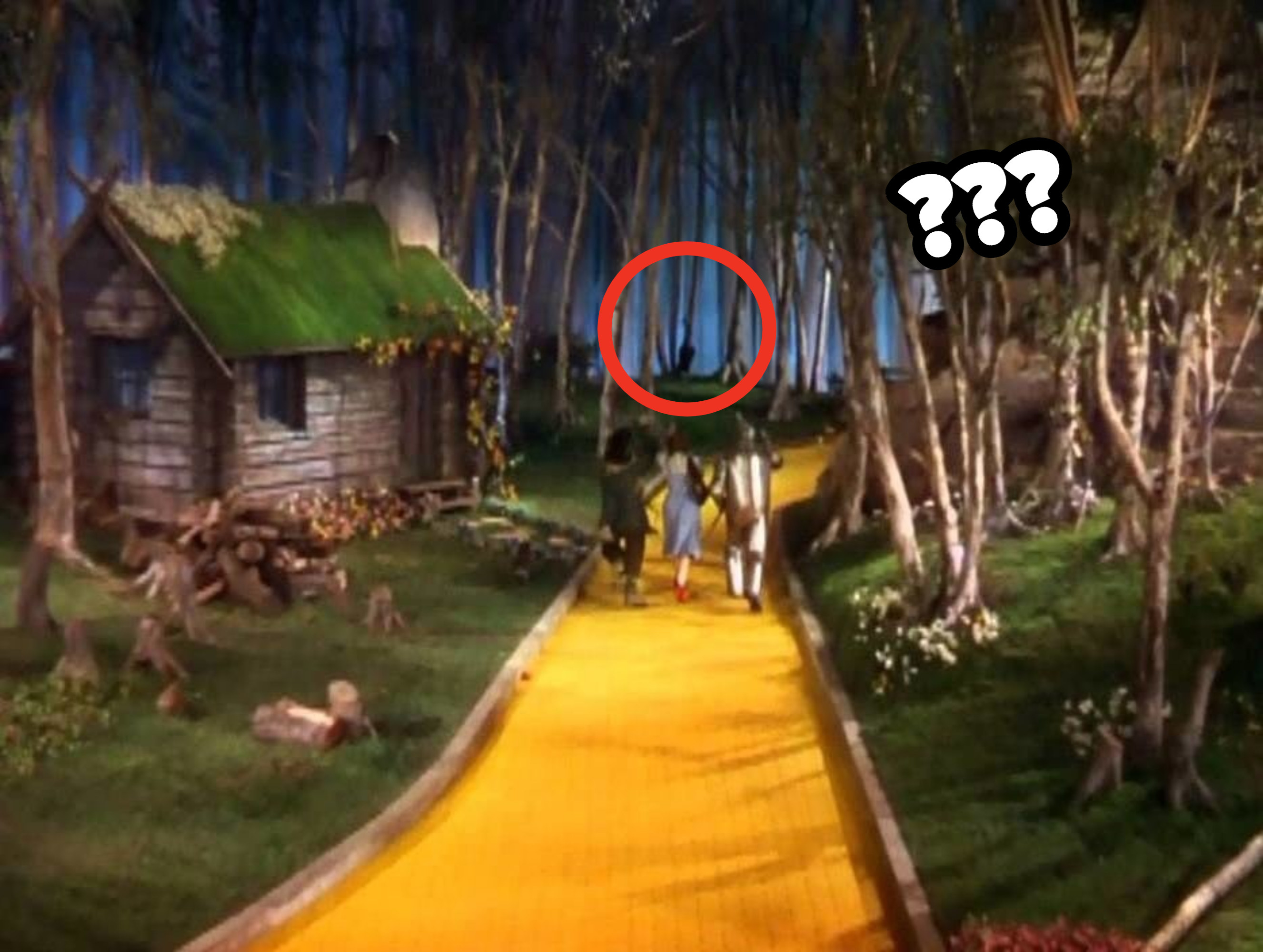 Dorothy, the Scarecrow, and the Tin Man skipping arm in arm while a mysterious black object hangs from a tree in the background