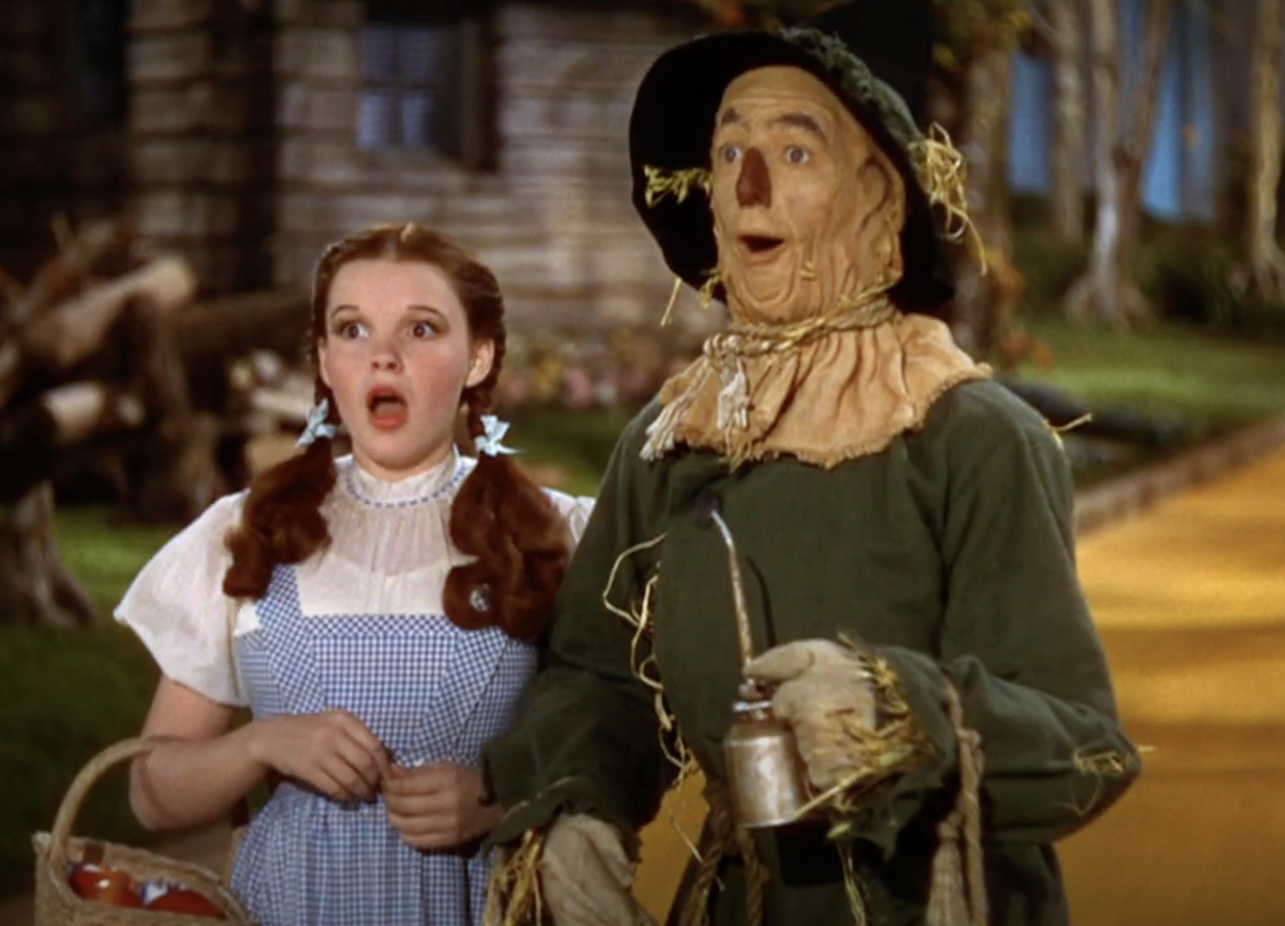 Dorothy and the Scarecrow making a shocked expression while meeting the Tin Man