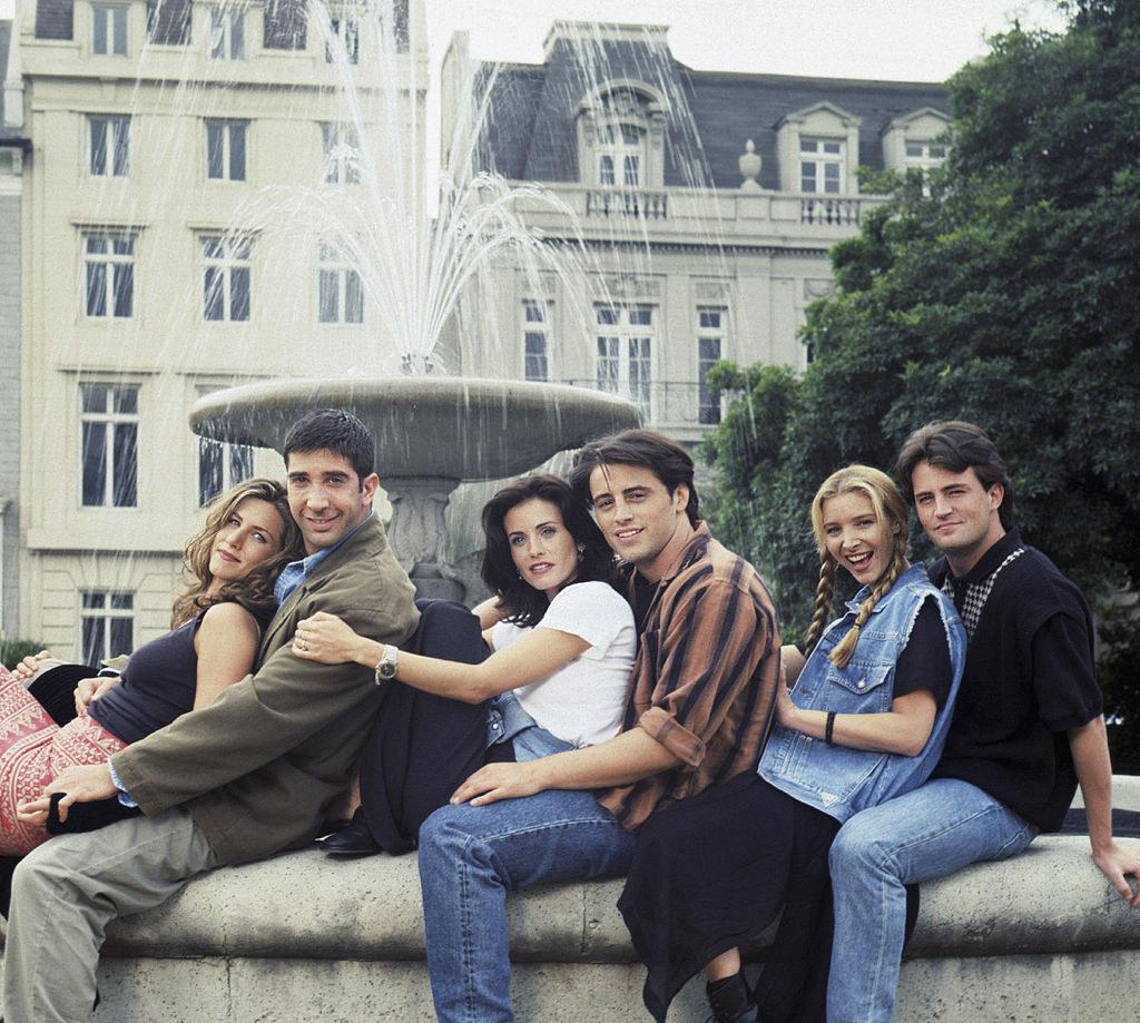 "Jennifer Aniston, David Schwimmer, Courteney Cox, Matt LeBlanc, Lisa Kudrow, and Matthew Perry sitting on the fountain edge for Season 1 of ""Friends"""