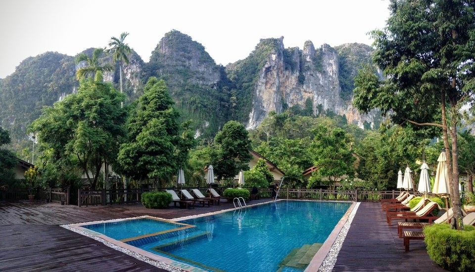 A hotel pool view with a mountainous backdrop in Ao Nang, Thailand