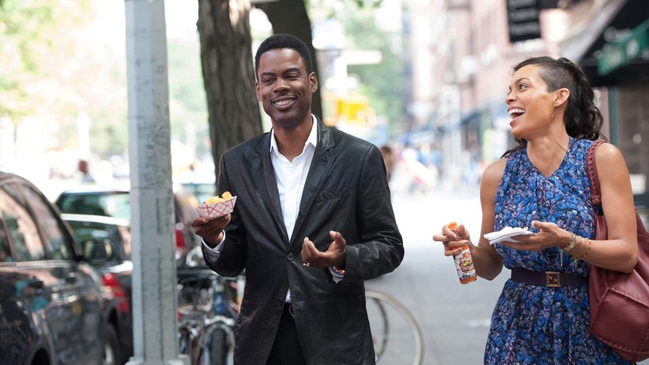 Chris Rock as Andre and Rosario Dawson as Chelsea walking down the street while eating