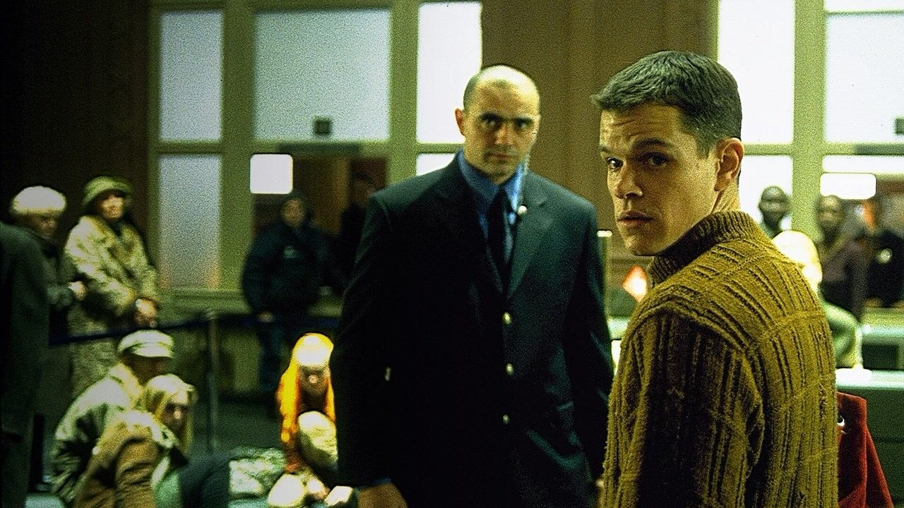 Matt Damon as Jason Bourne sitting in a room with a man and people in military uniforms
