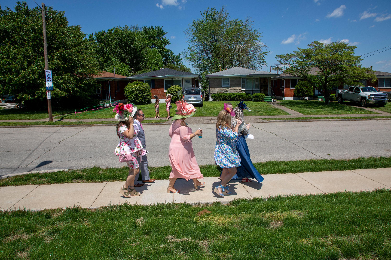 Three women in fancy dresses walk through a neighborhood on their way to the Kentucky Derby