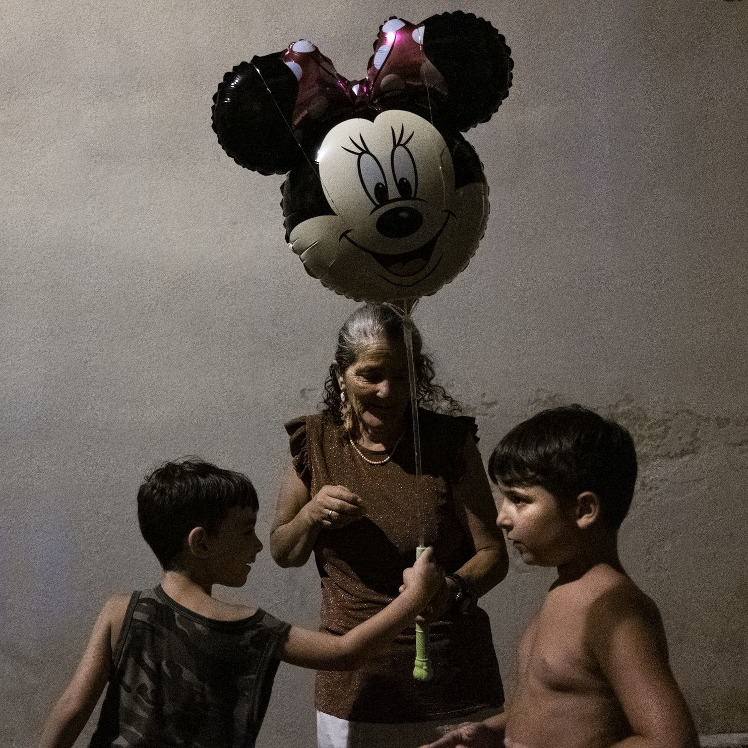 Two young boys play in front of an older Italian woman holding a Minnie Mouse balloon