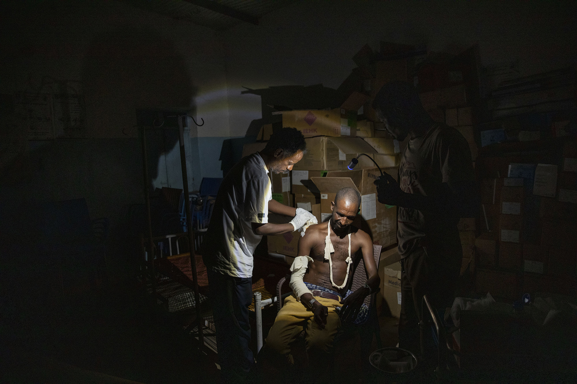 A man cleans a wound and makes a cast for a refugee