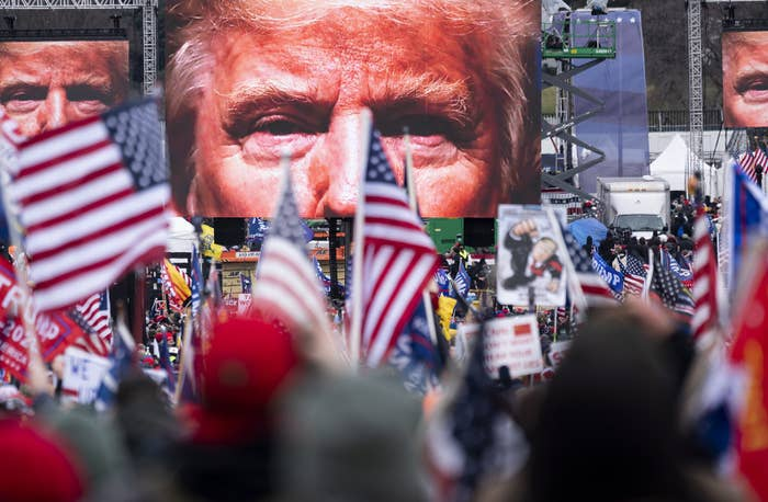 A close-up of Trump's eyes appear on three video screens playing in front of a crowd wearing red caps and waving US flags and Trump flags