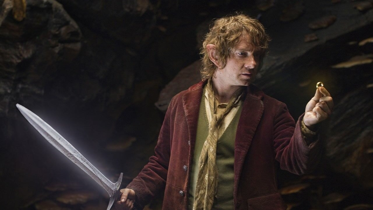 Martin Freeman as Bilbo Baggins, holding a sword and the ring