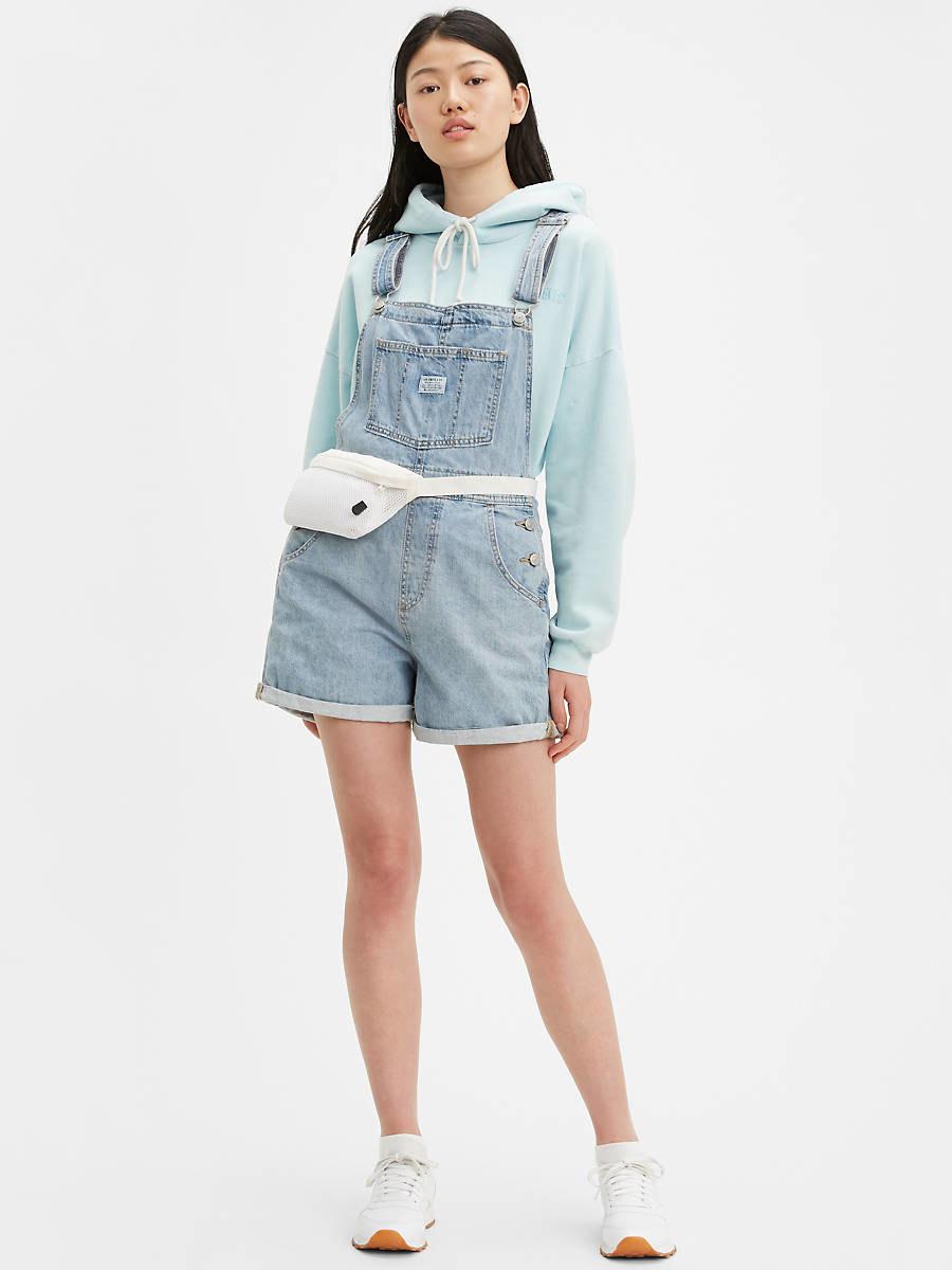 model wearing light wash short overalls with large front pocket