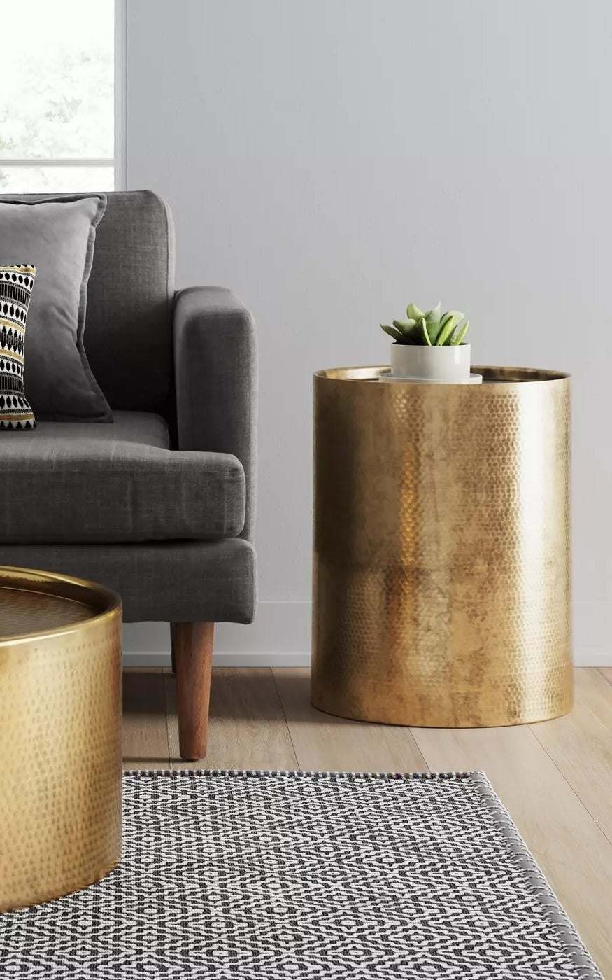 A cylindric gold accent table in a living room with a hammered exterior