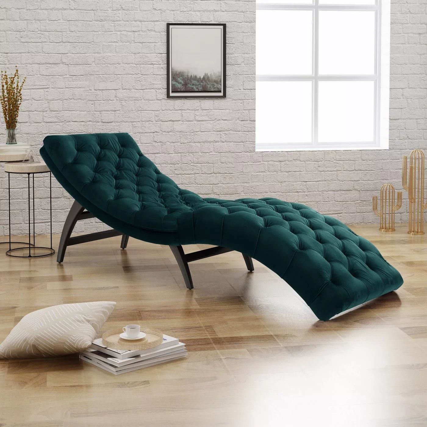 The teal chaise with a curved shape and tufted velvet texture in a living room