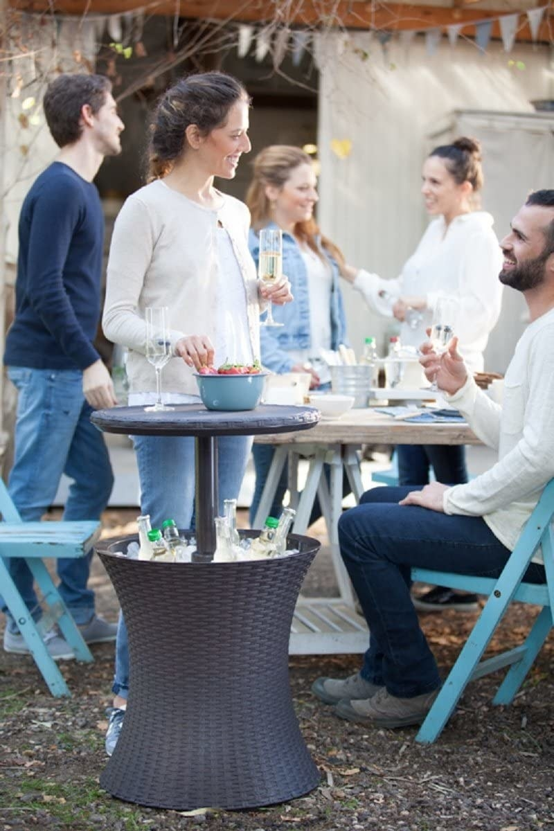 the table with drinks and ice in the base and food on top surrounded by people talking