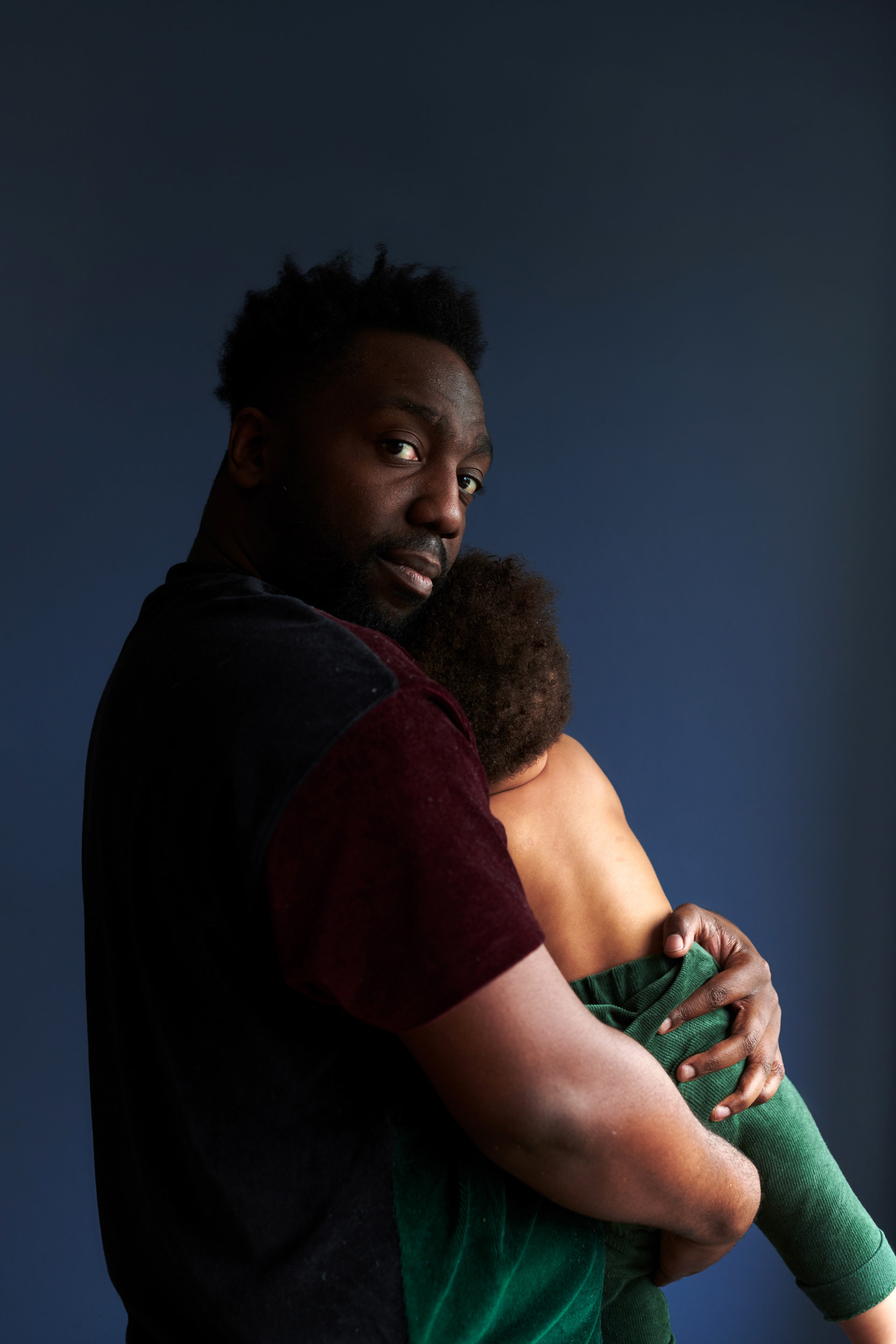 A man looking at the camera holds his young son, who is looking away from the camera