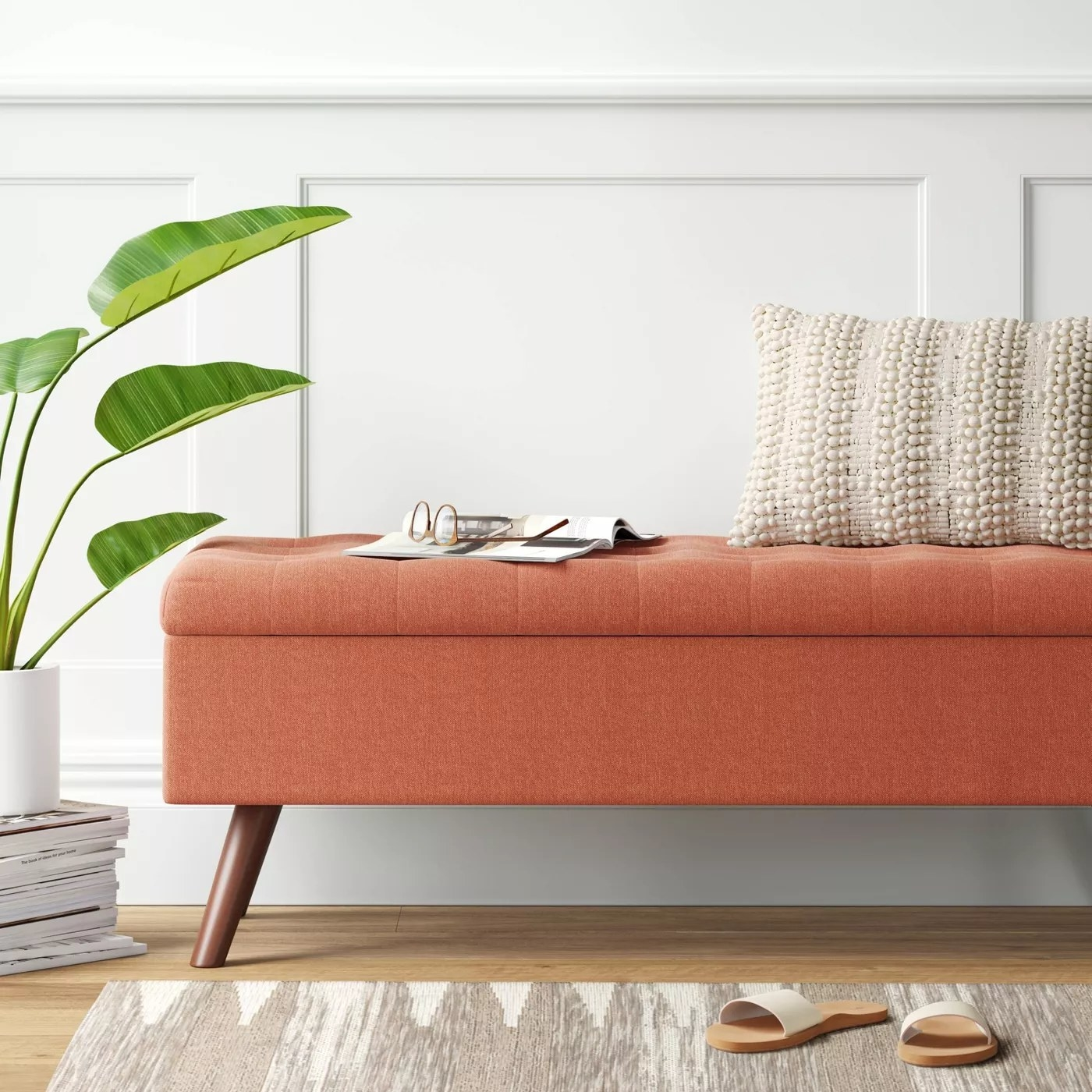 The tufted storage bench with wooden legs in an entryway