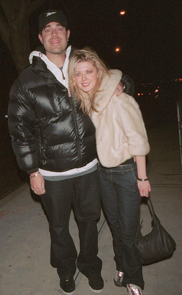 Carson Daly and Tara Reid smiling on a sidewalk