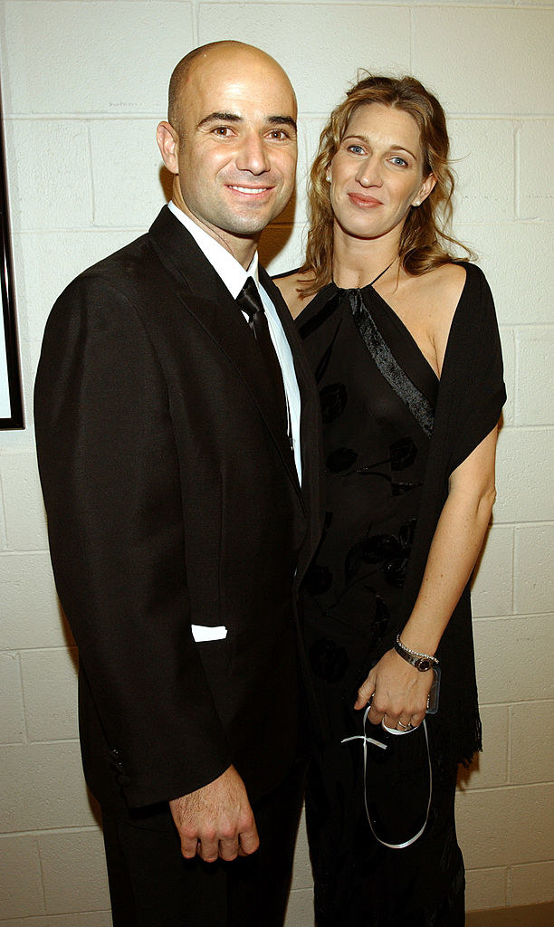 Andre Agassi and Steffi Graf standing in front of a cinderblock wall