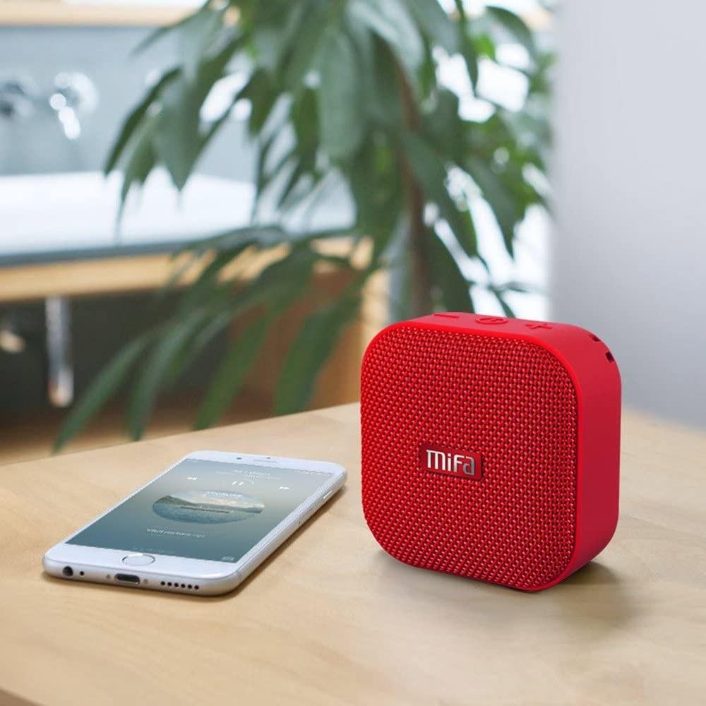 The speaker on a desk beside a cellphone