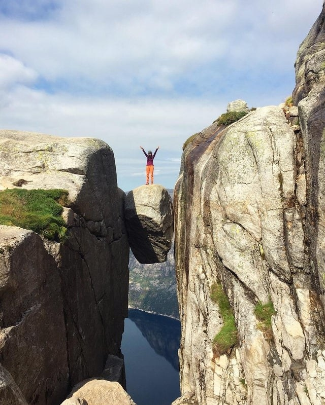 Someone standing on a suspended boulder in Kjeragbolten, Norway