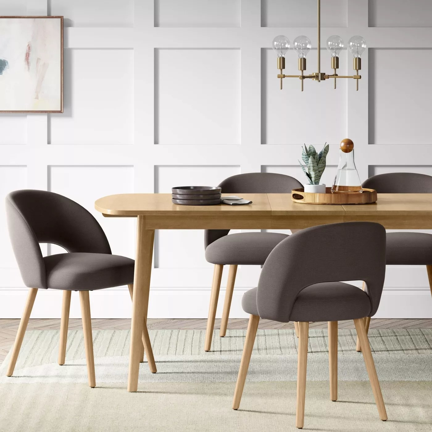 Several of the dining chairs with a cushioned open back and seat and wooden legs in a dining room