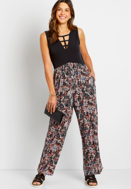 model wearing the jumpsuit with a sleeveless black bodice with strappy V-neck and black, white, blue, and red floral pants