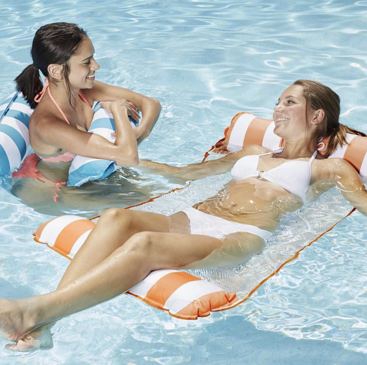 two people in the pool with the floaties one straddling and one lying
