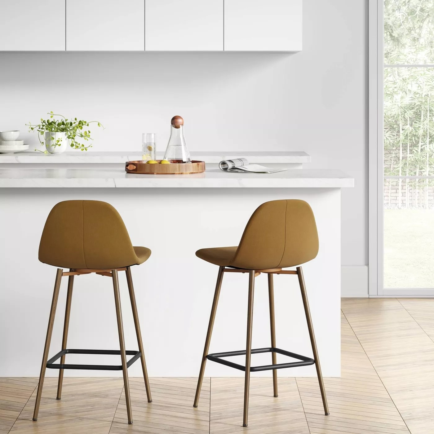 Two mustard-colored bar stools with metal legs in front of a kitchen island