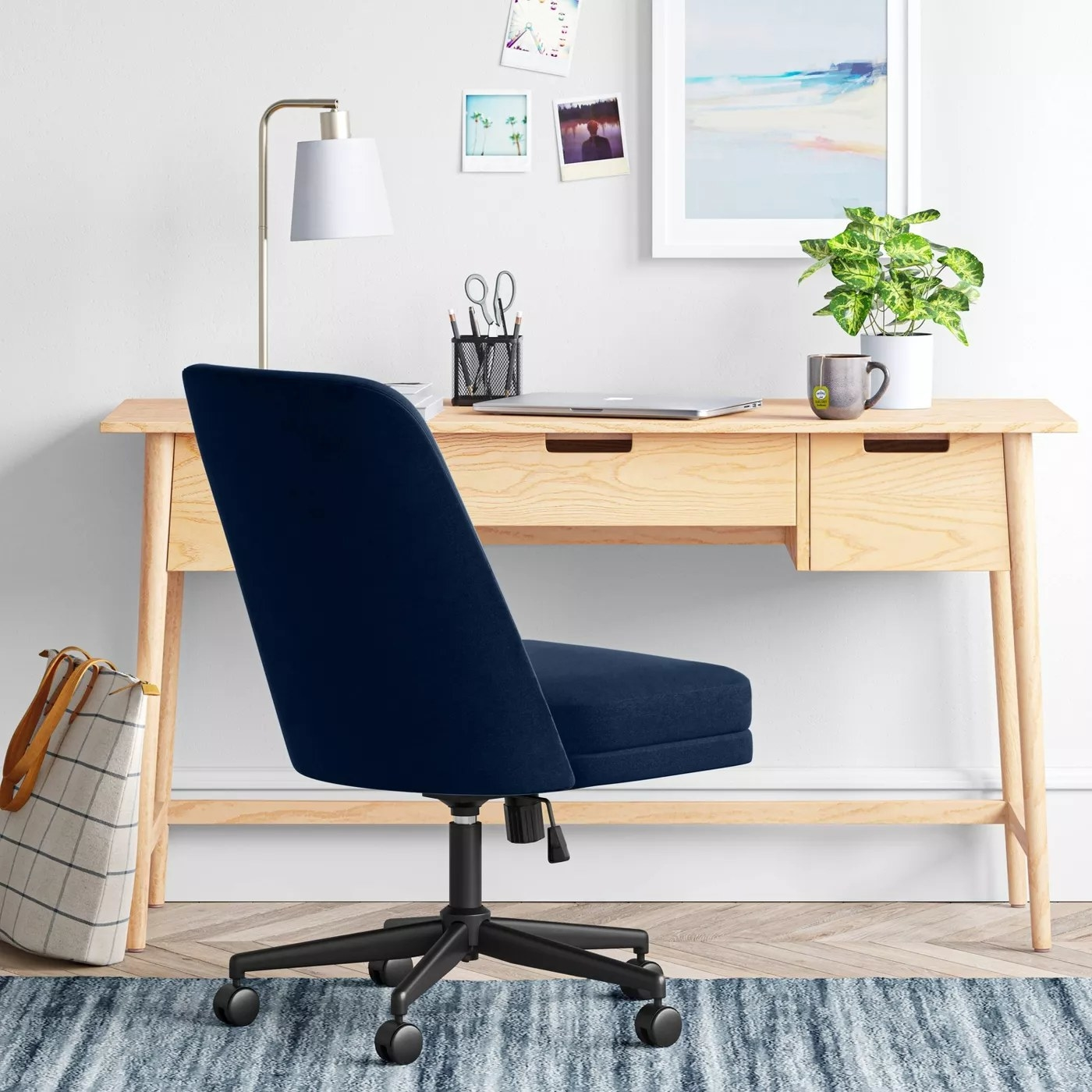 The armless, navy chair on wheels in a home office