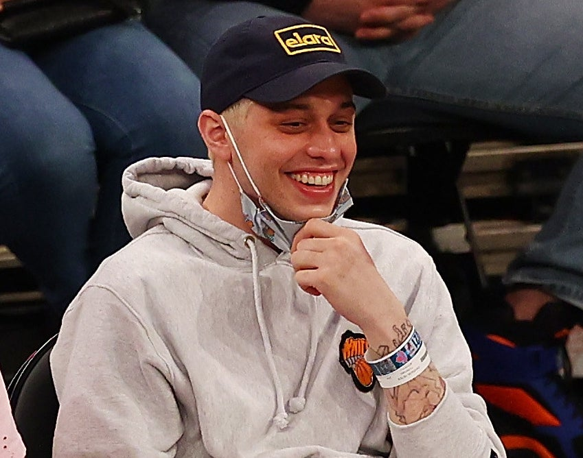 Pete pulls his mask down to smile at a basketball game