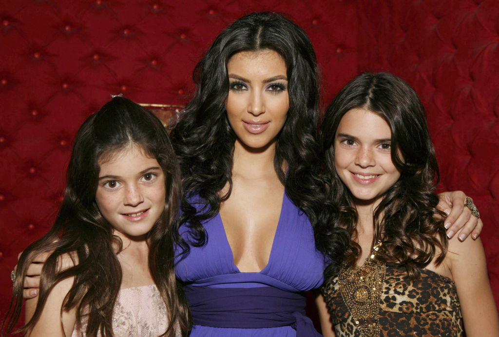 A young Kendall posing for a photo with Kim and Kylie