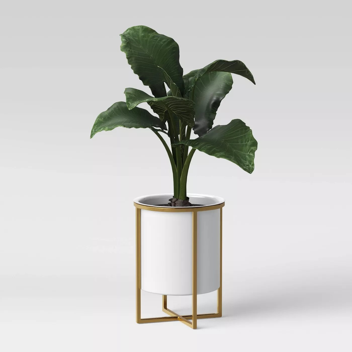 The white circular planter with a brass frame and a plant inside