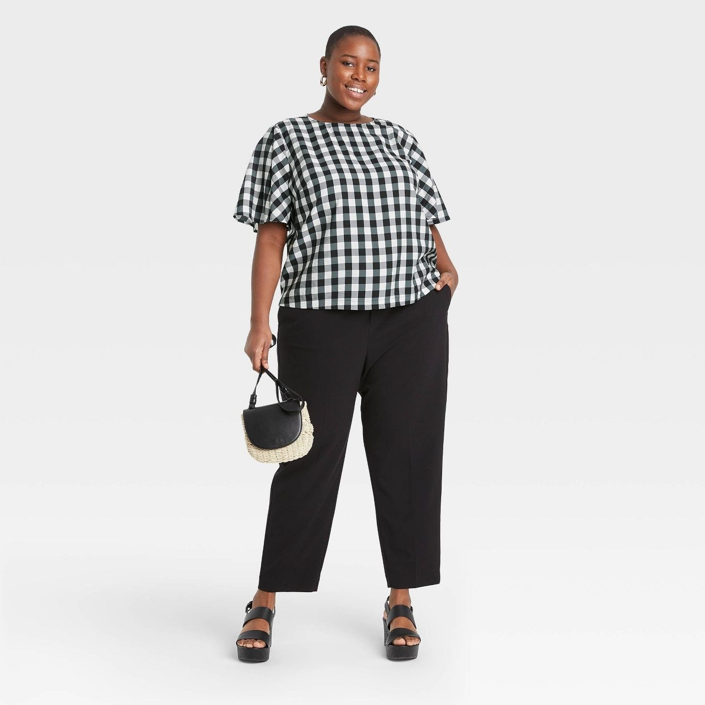 a plus size model wearing the black and white gingham flutter short sleeve top with black trousers