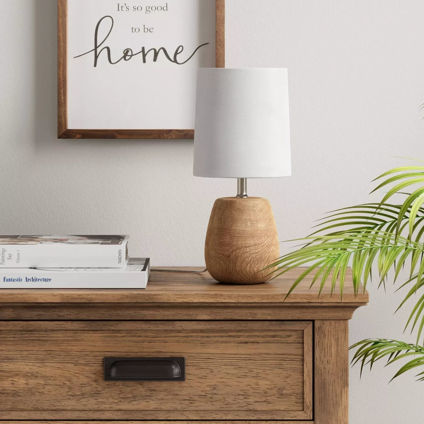 The wooden lamp with a white circular shade on a table