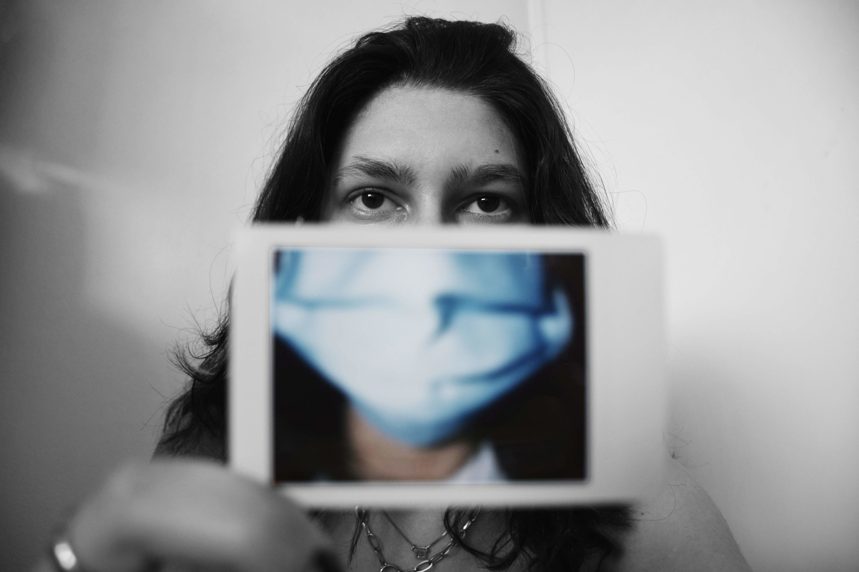 A woman in a mask in a black-and-white photo holds a color Polaroid of a mask up to her face