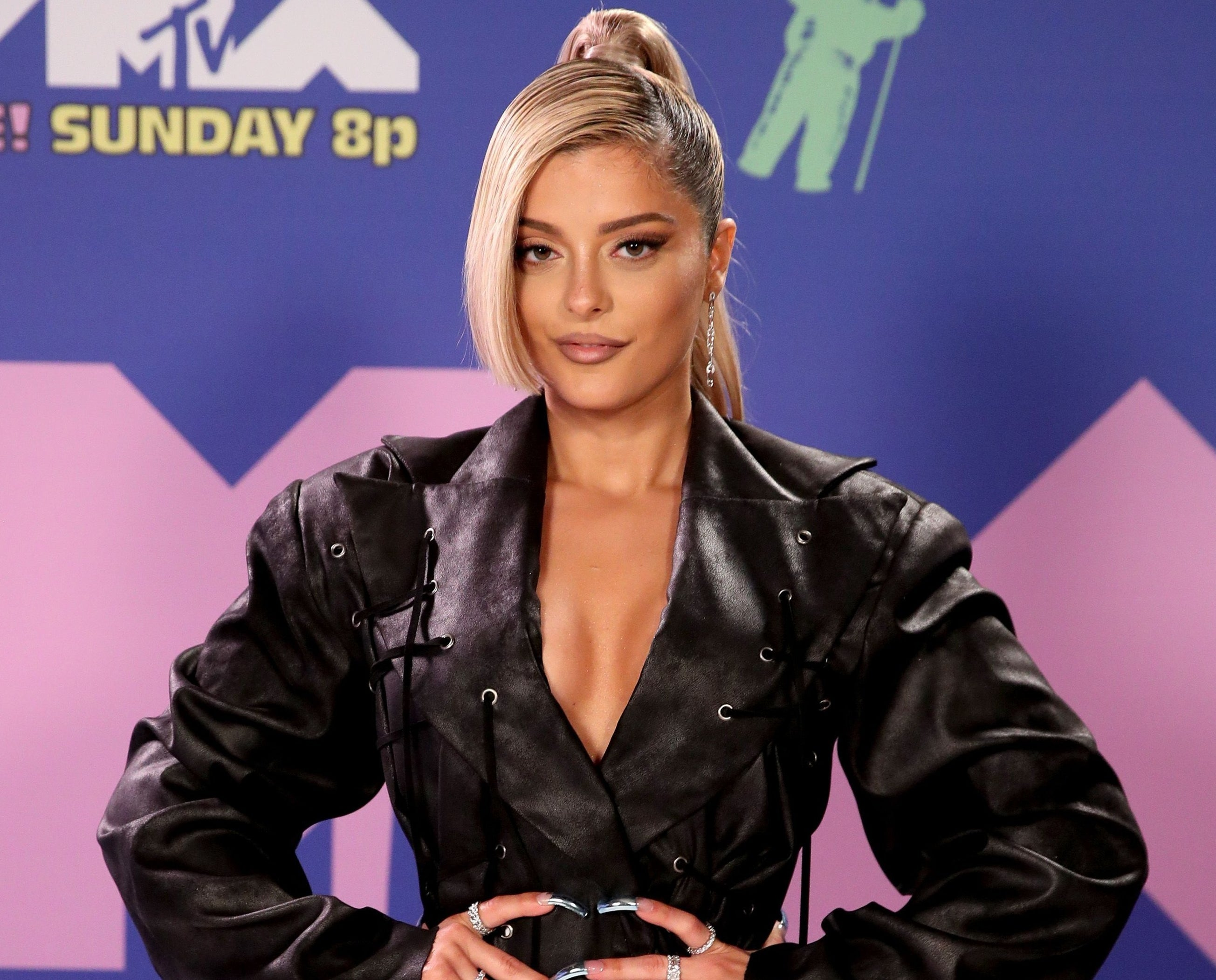 Bebe wears blonde hair in a ponytail with a leather dress at an event