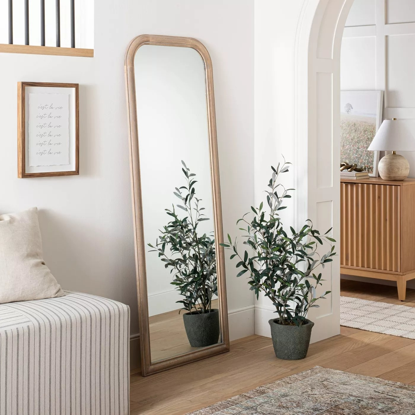 The full-length mirror with a wooden frame and rounded edges in a living room
