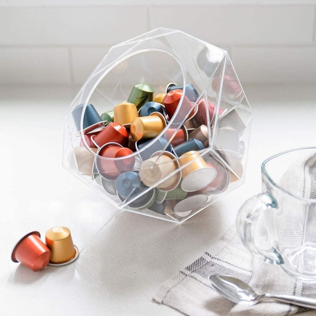 Several coffee pods in the bowl beside a mug