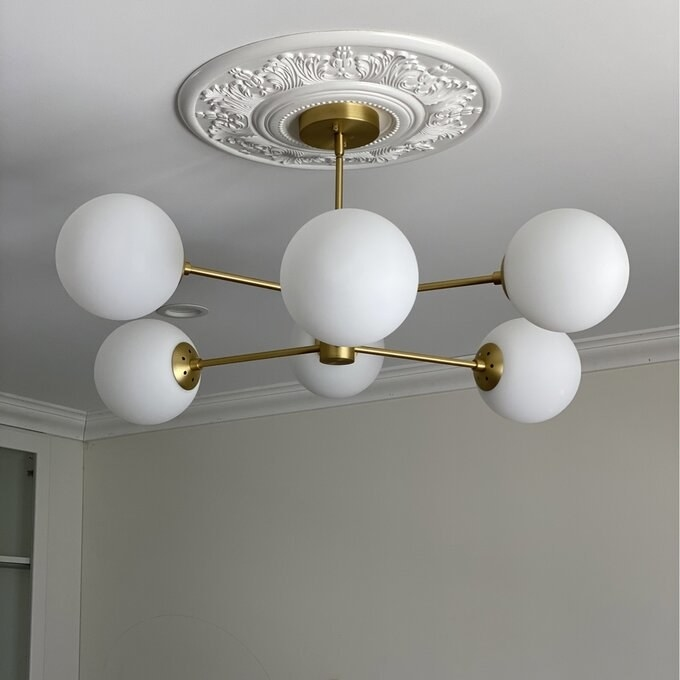Light fixture with white bulbs and gold metal frame