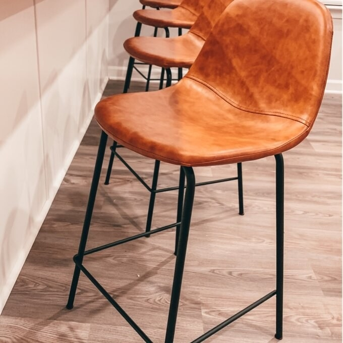 Camel colored leather stools with black metal frame