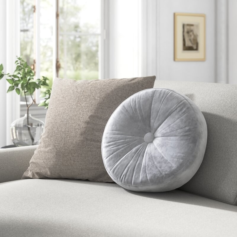Gray tufted pillow with button in the middle