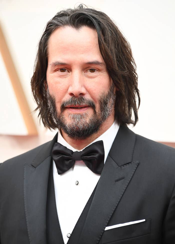 Photo of Keanu Reeves in a classic three-piece suit and bow-tie
