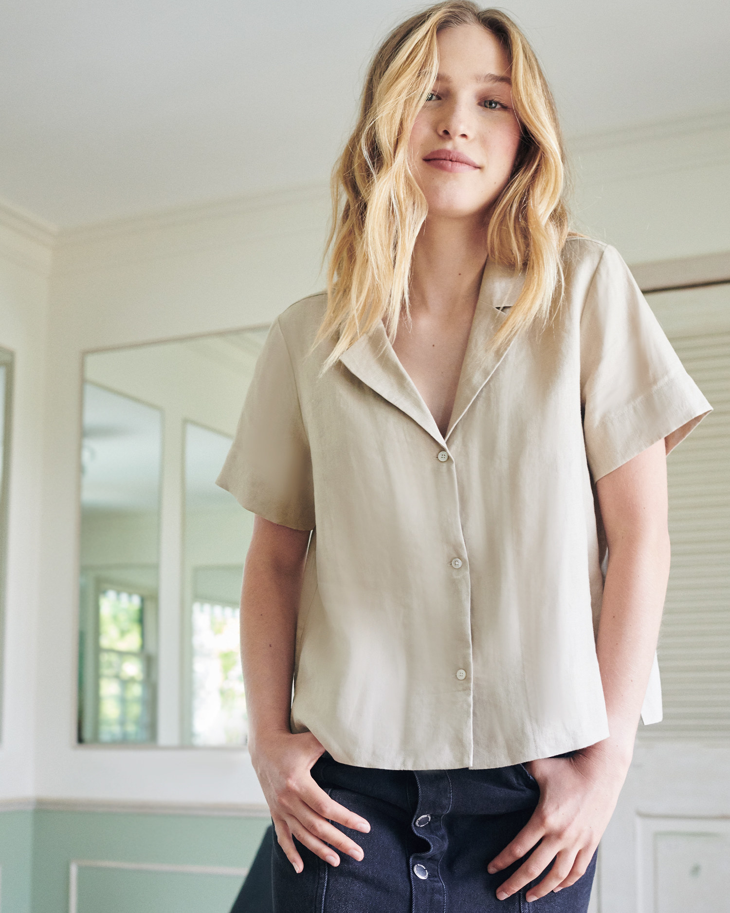 a model wearing the organic linen short sleeve shirt in the color driftwood