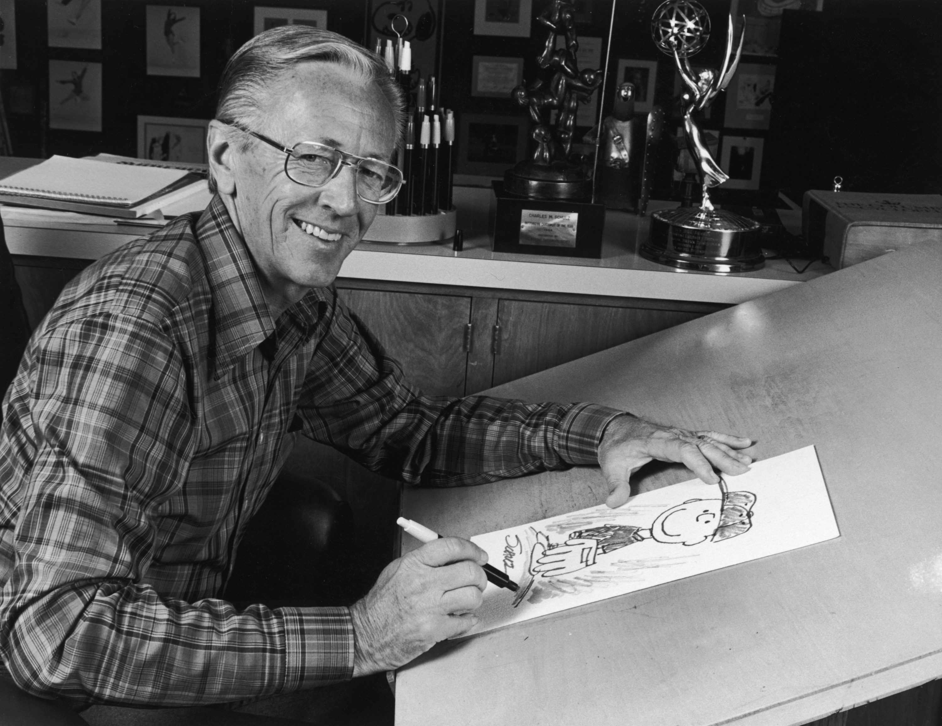 Black-and-white photo of Charles Schulz at a table drawing a sketch of Peanuts character Charlie Brown