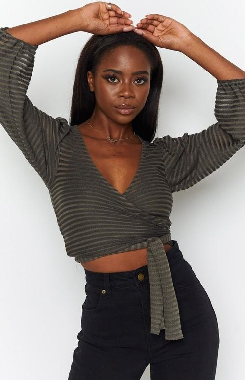 a model wearing the khaki wrap top with high waisted black pants