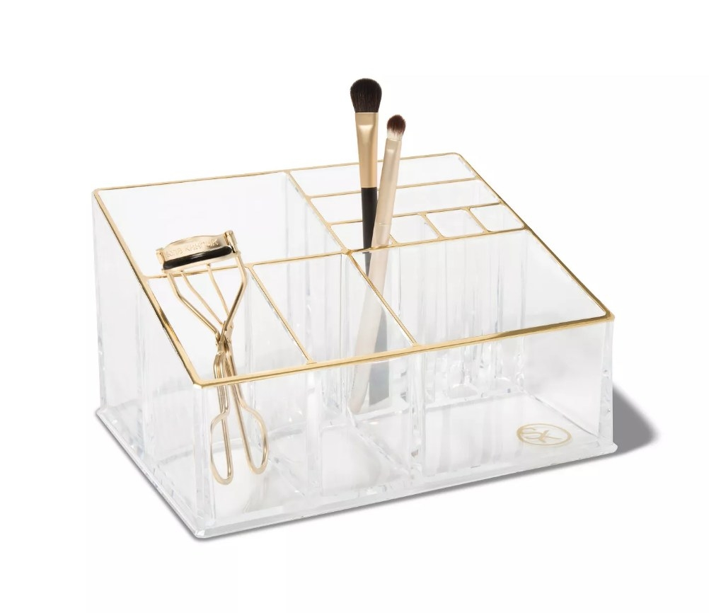 Clear plastic makeup organizer with gold detailing, eyelash curler in one compartment, makeup brushes in another