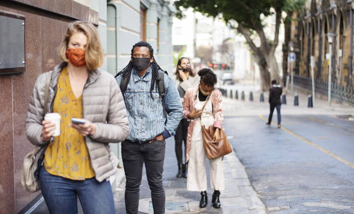 A group of people walking on the side walk, all wearing masks