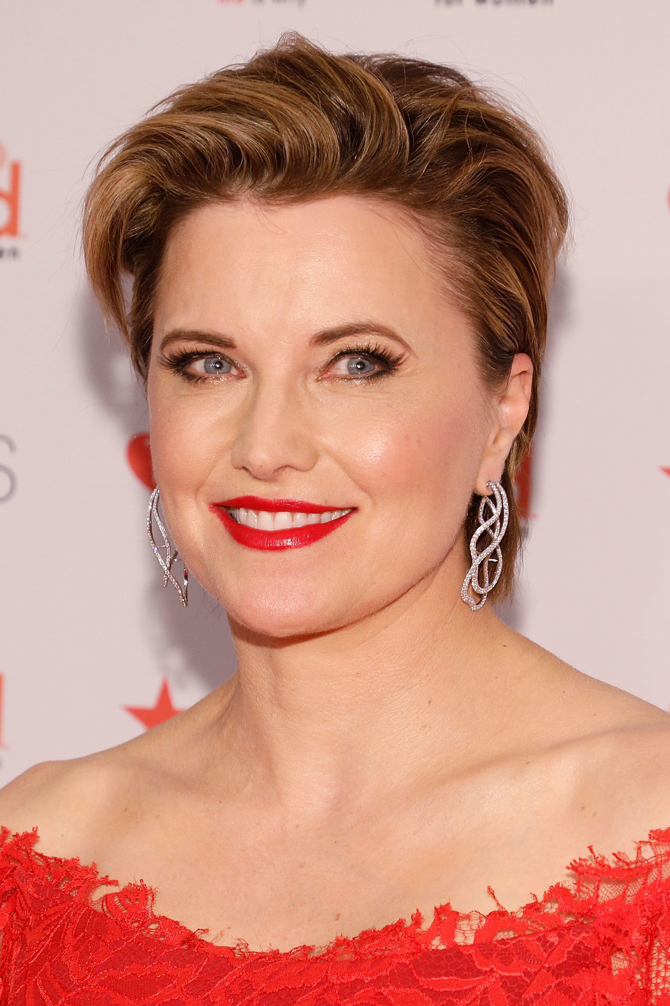 Lucy Lawless in a red dress and red lipstick at a premiere event