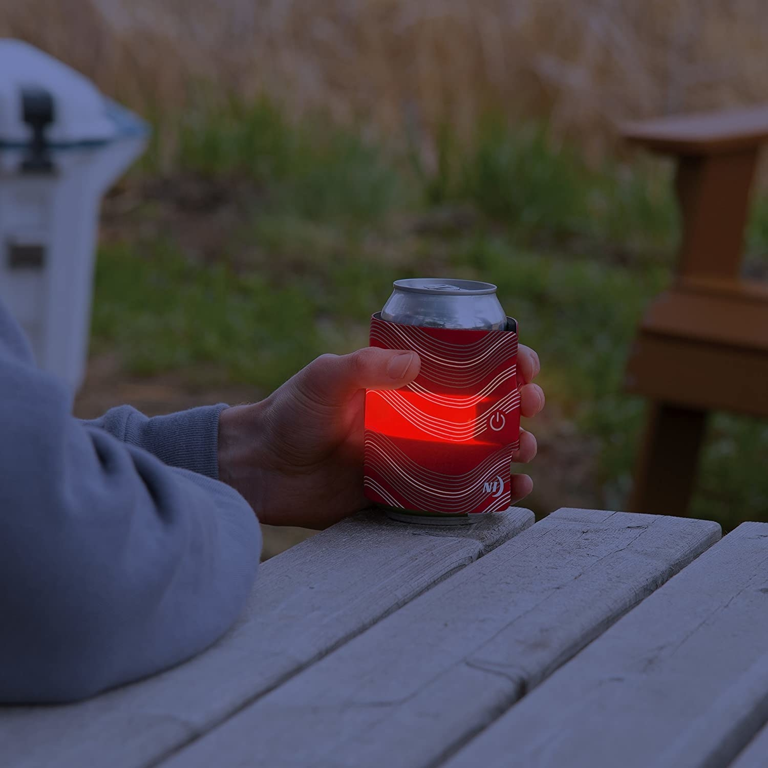 A person holding their drink with the light-up holder on it