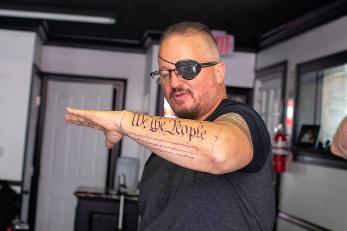 """A man with an eyepatch holds up his forearm, which has a tattoo that reads """"We the people"""""""