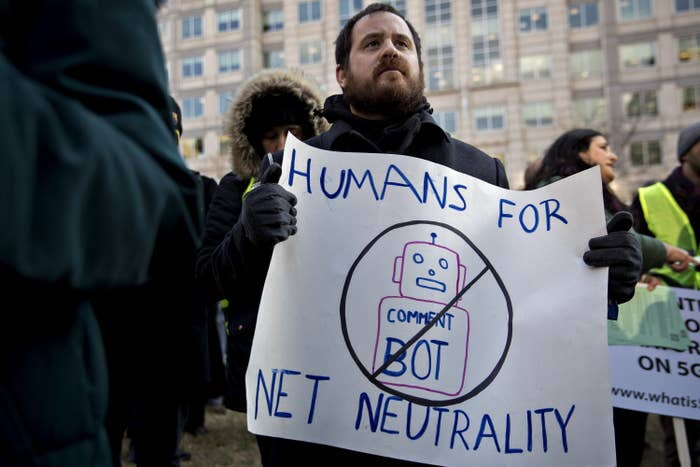 """A demonstrator holds a poster that says """"Humans For Net Neutrality."""" The poster also contains a drawing of a robot, crossed out and with """"Comment Bot"""" written on its torso."""