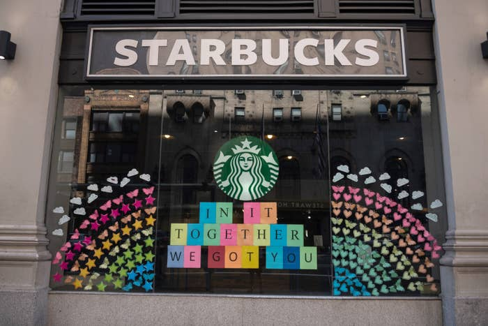 """A Starbucks window displays a sign reading """"In it together, we got you"""""""
