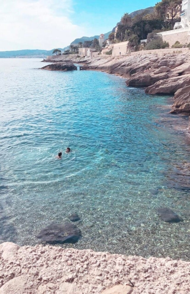 People swimming in a peaceful, clear-blue cove in Southern France